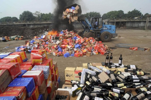 Bottles of fake wine are destroyed in Nanning. Credit: Reuters