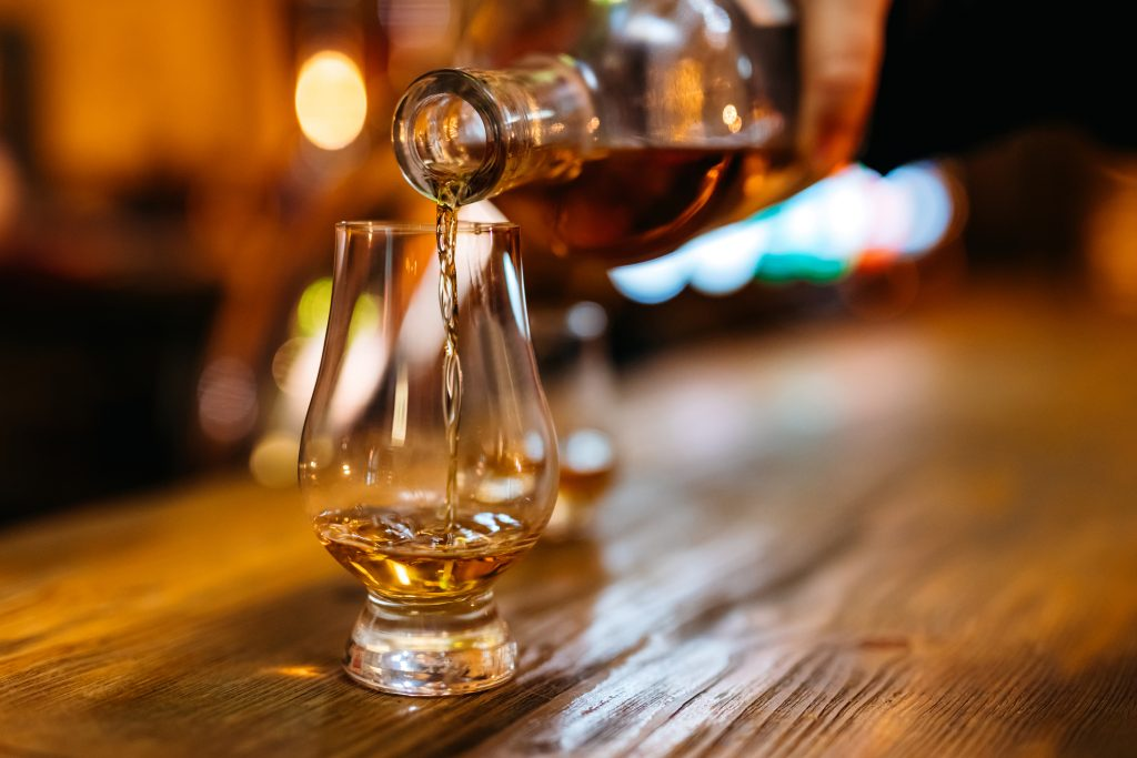 Fake bourbon: Pouring whiskey in glass