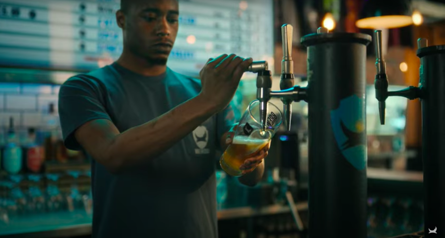 BrewDog employee pouring a pint: BrewDog launches \'Beer for All\' carbon negative ad campaign