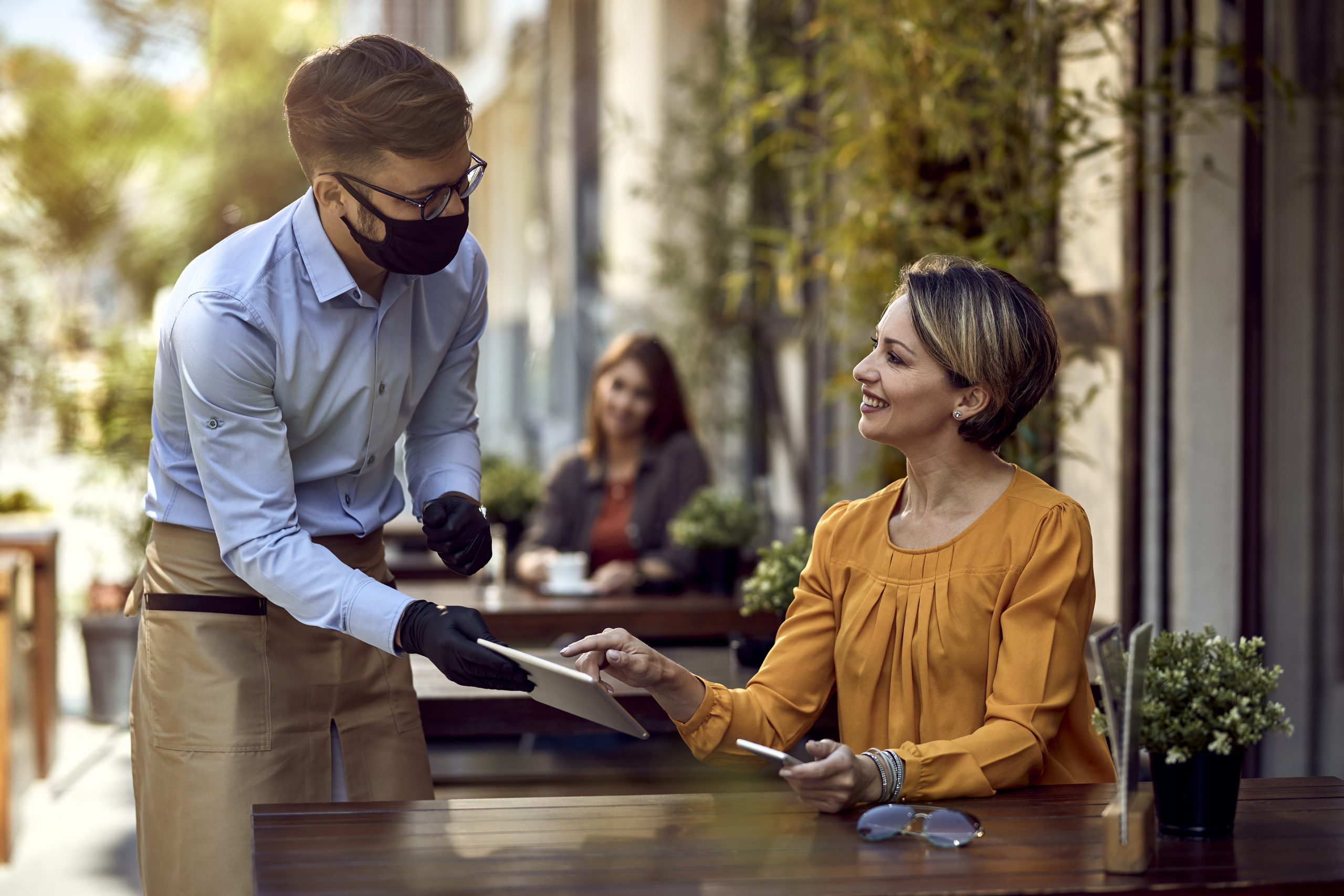 waiter serving woman: hospitality in crisis with staggering number of roles unfilled