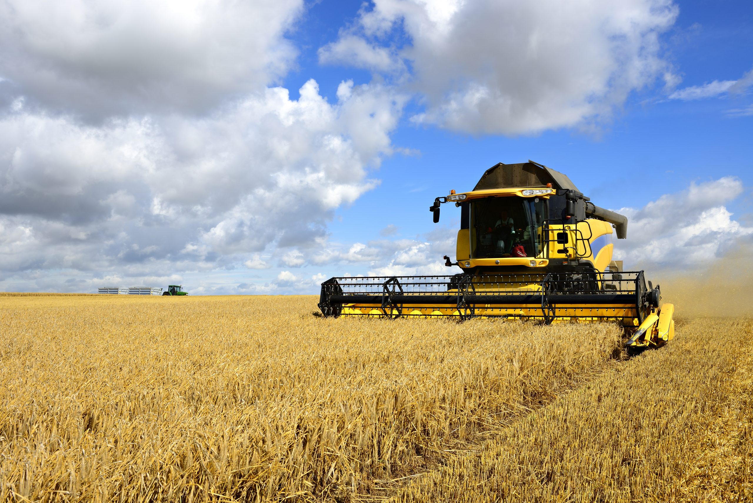 Combine Harvester and Tractor in Barley Field during Harvest: Heineken UK launches low carbon barley trial