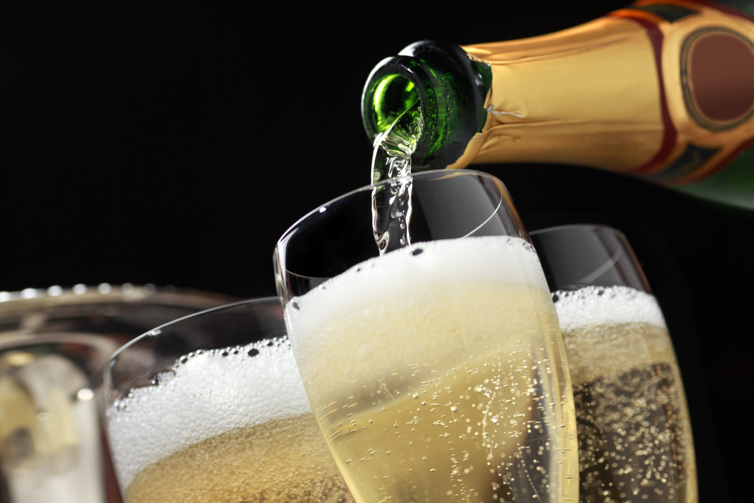 Champagne being poured into champagne glasses: Five top tips for serving a glass of Champagne