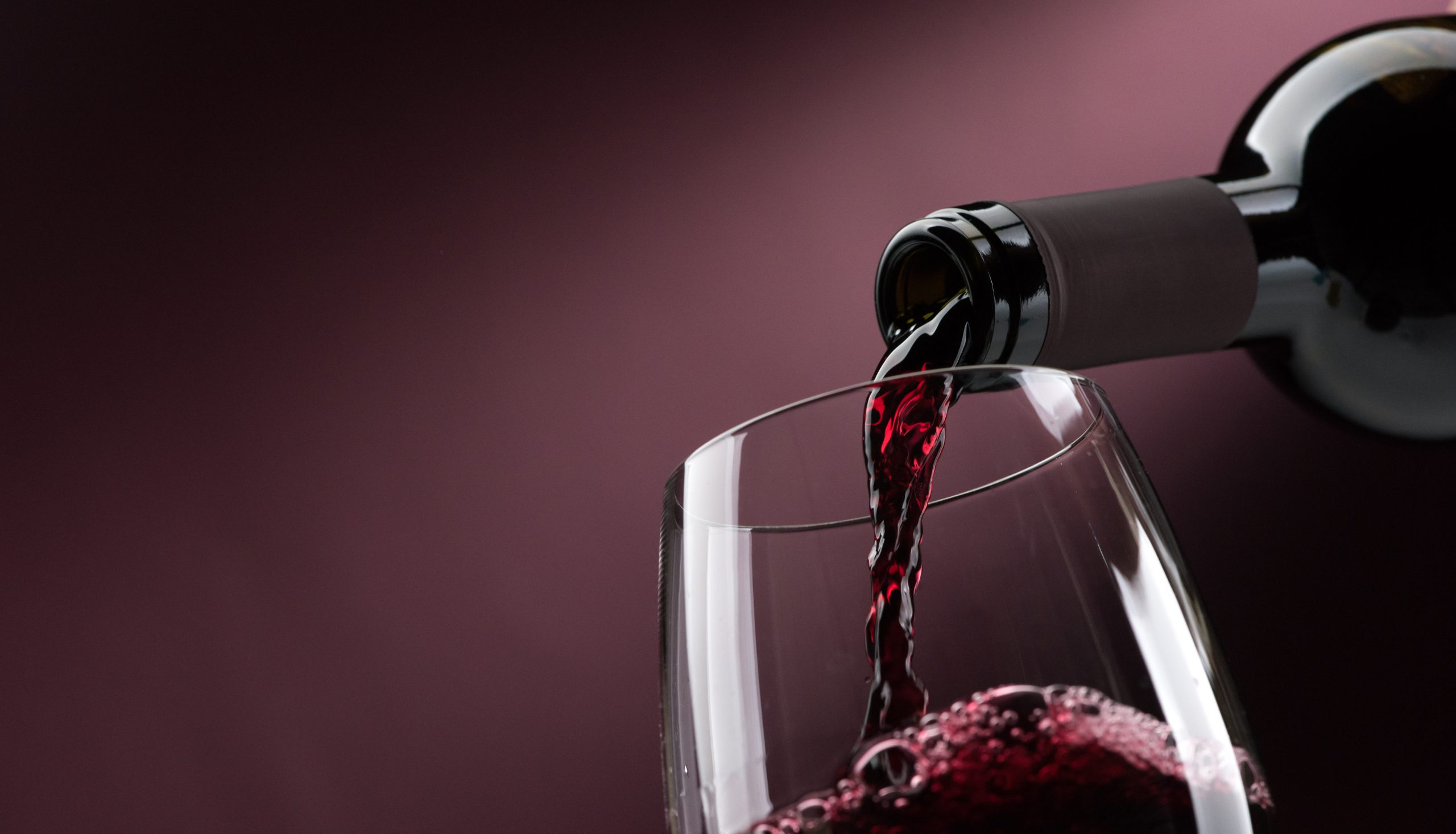 red wine poured bottle to glass: fine wine sales boosted by pandemic, research reveals
